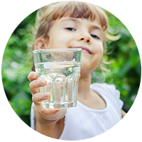 Photo of a child holding a glass of water out toward the camera.